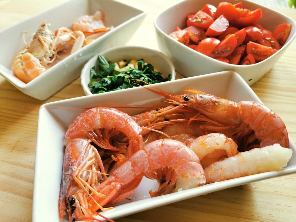 peeled and whole prawns in white bowl with chopped tomatoes in white bowl and peeled and whole scampi in white bowl