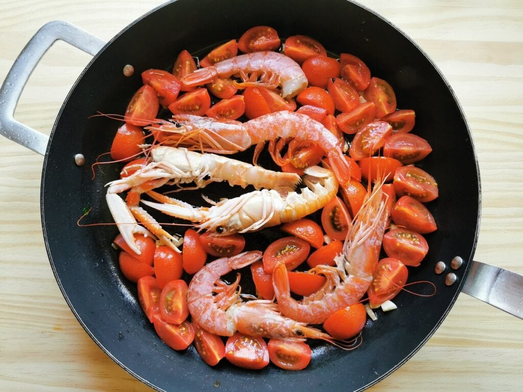 whole prawns and scampi inskillet with tomatoes