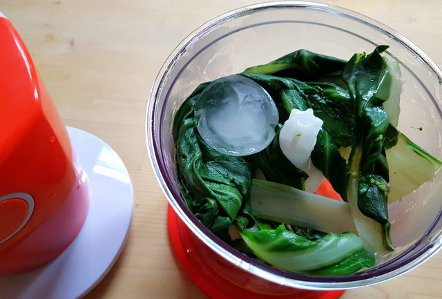 chard leaves with ice and olive oil in blender
