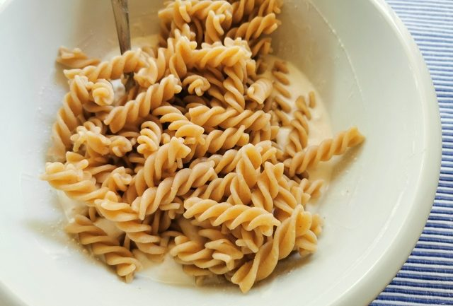 cooked fusilli in white bowl with ricotta