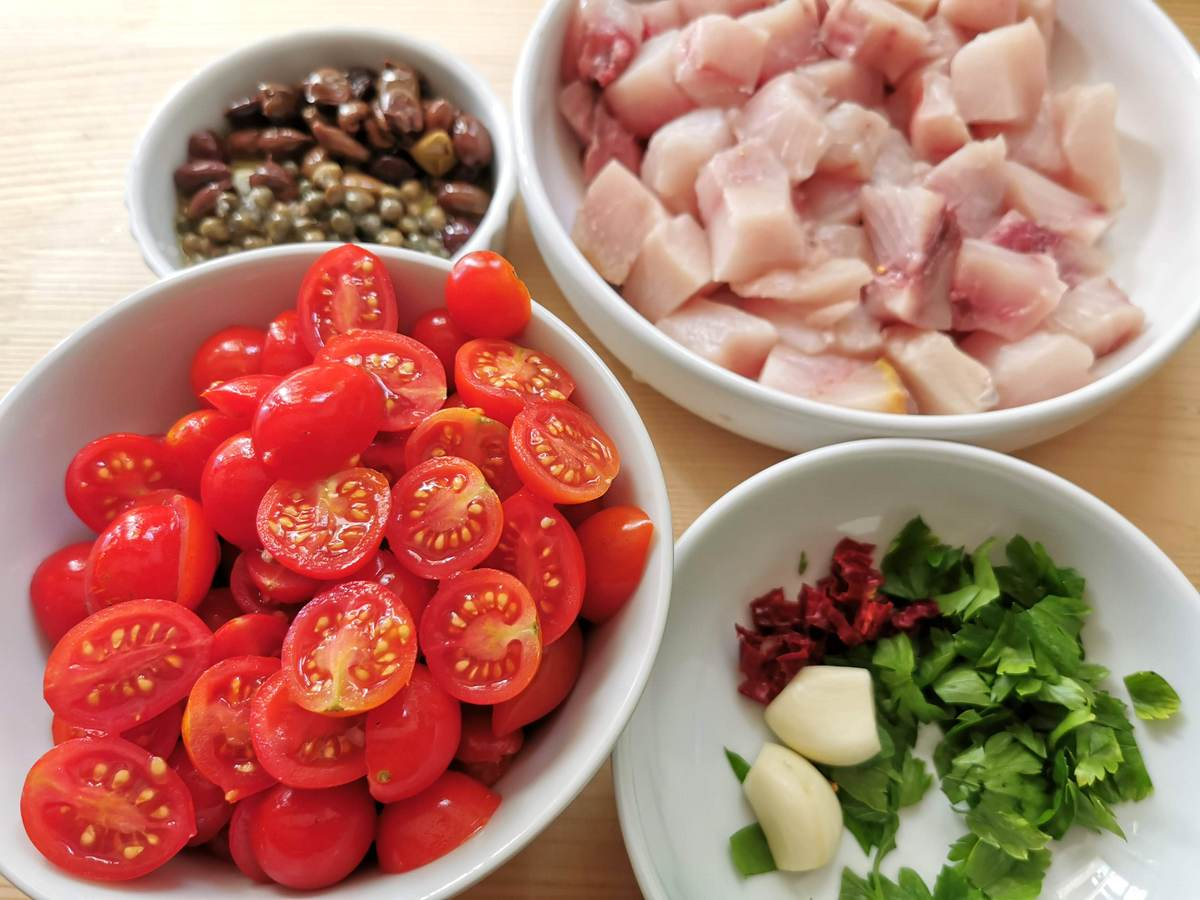 tomatoes, swordfish, and other ingredients prepared for cooking