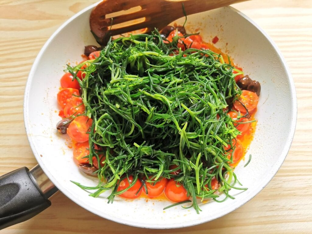 Blanched agretti in frying pan with other sauce ingredients