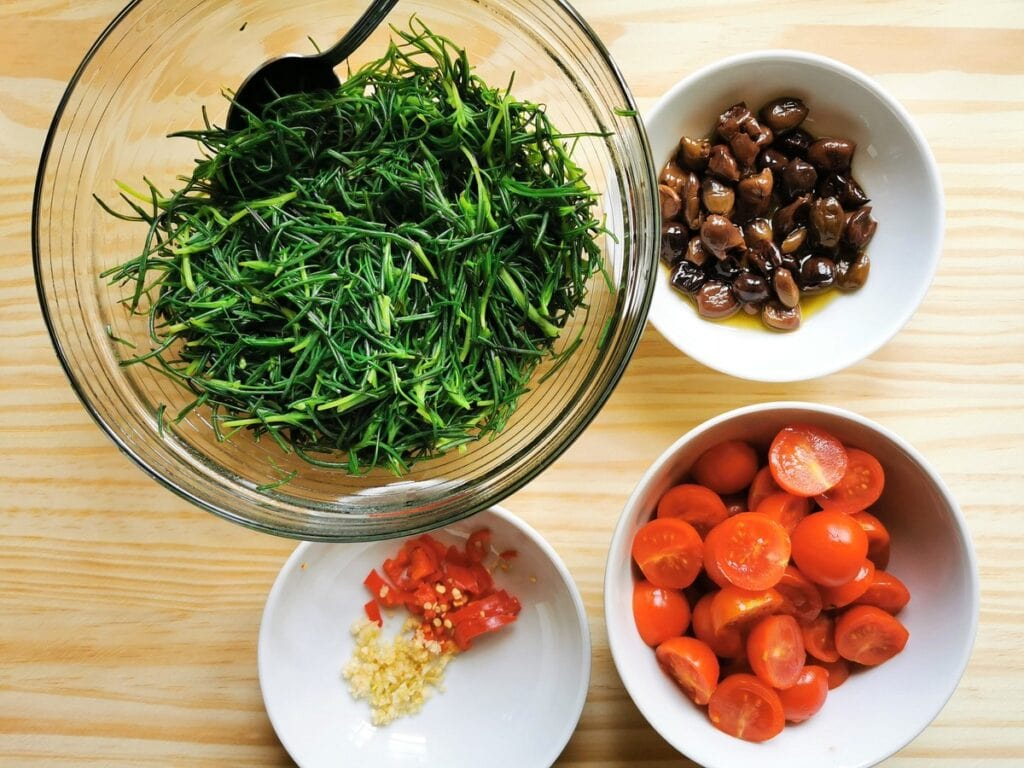 halved cherry tomatoes in white bowl. Blanched agretti in white bowl. chopped garlic and peperoncino in white bowl and pitted olives in white bowl.