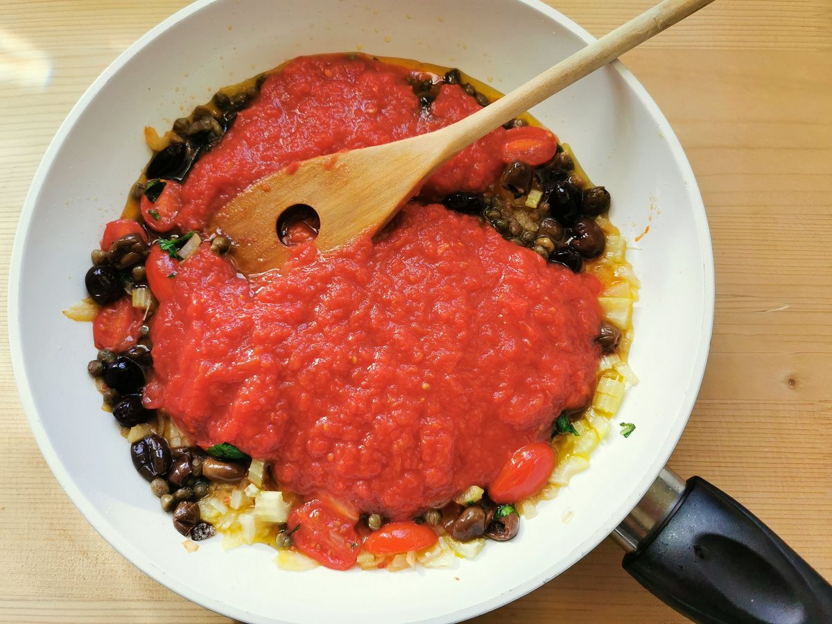 tomato passata added to other ingredients in frying pan.