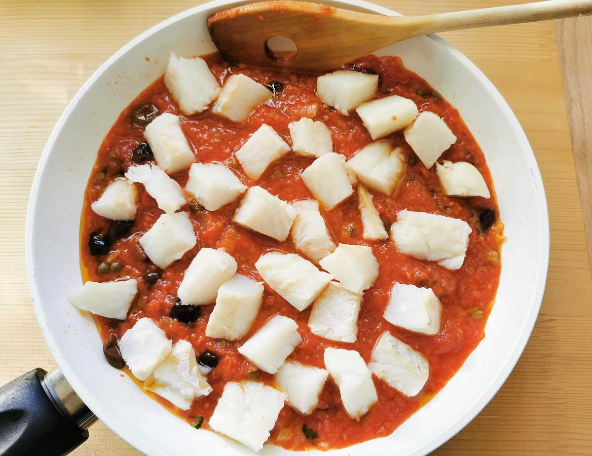 cubes of baccalà salt cod added to sauce in frying pan