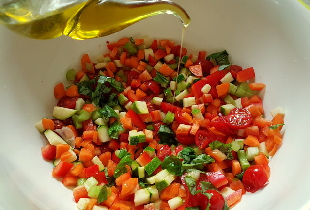 pouring olive oil on chopped vegetables for summer tagliolini pasta recipe