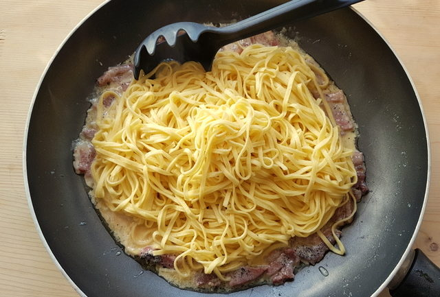 cooked tagliolini with San Daniele sauce in frying pan