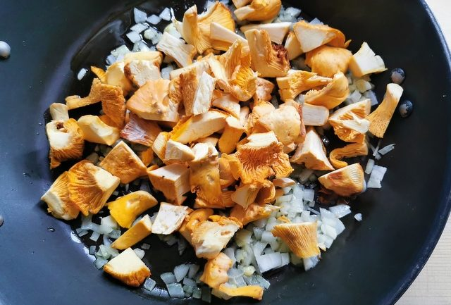 chanterelle mushroom pieces in skillet with chopped onions and garlic