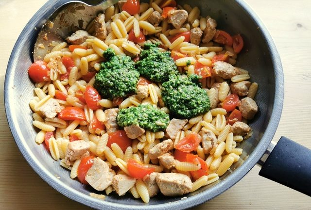 homemade basil pesto added to pasta, tuna and tomatoes in frying pan