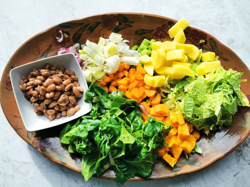 Cooked beans and peeled, washed and chopped vegetables on an oval terracotta plate