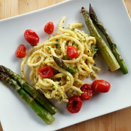 Tuscan pici pasta all'etrusca with asparagus and cherry tomatoes on white plate