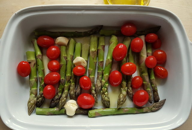 Asparagus and cherry tomatoes in white oven dish for Tuscan pici pasta all'etrusca