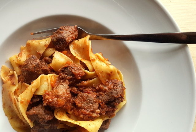 Tuscan wild boar ragu with pappardelle pasta in a white bowl