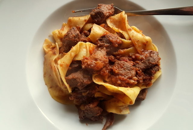 Tuscan wild boar ragu with pappardelle in a white bowl