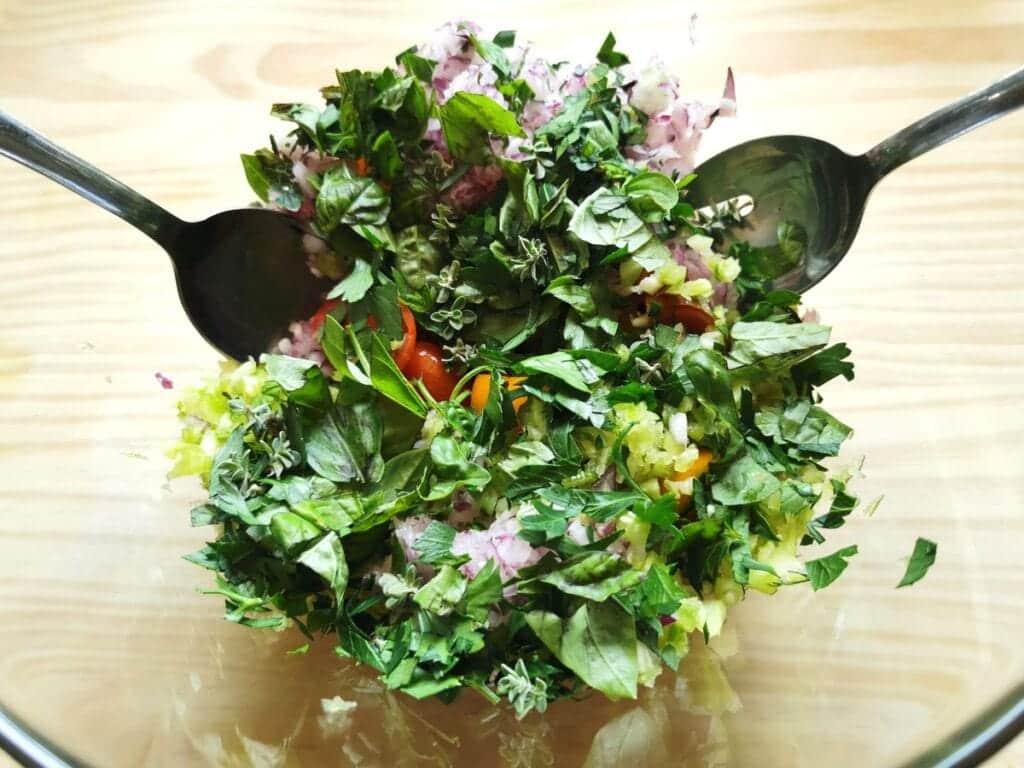 fresh basil, parsley and oregano added to veggies in glass bowl