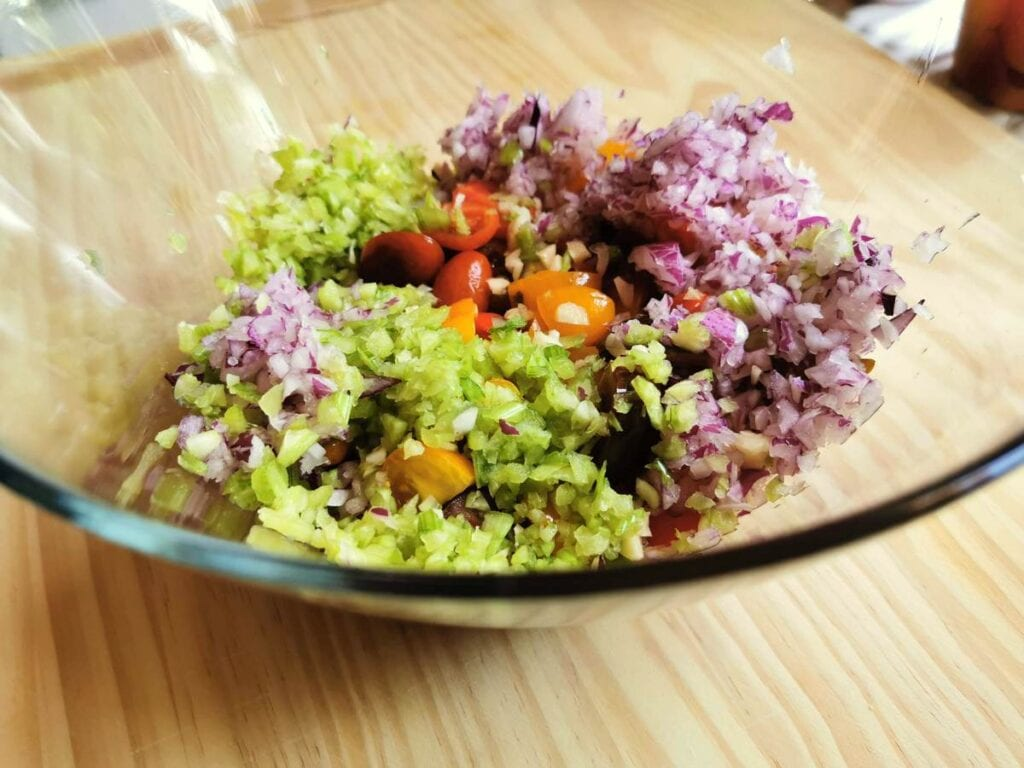 chopped vegetables and tomatoes in large glass bowl