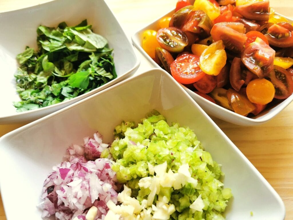 chopped onions, celery and garlic in white bowl. Chopped tomatoes in white bowl. Chopped parsley in white bowl