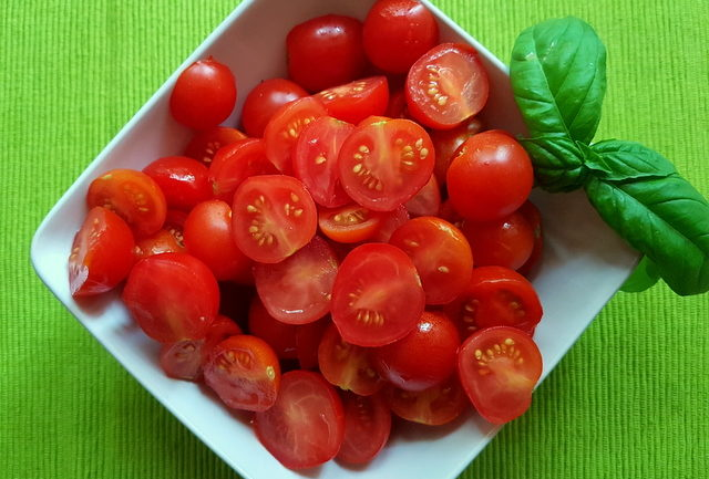 halved cherry tomatoes with basil in a white bowl