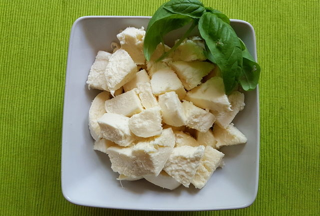 fresh mozzarella pieces in white bowl with basil