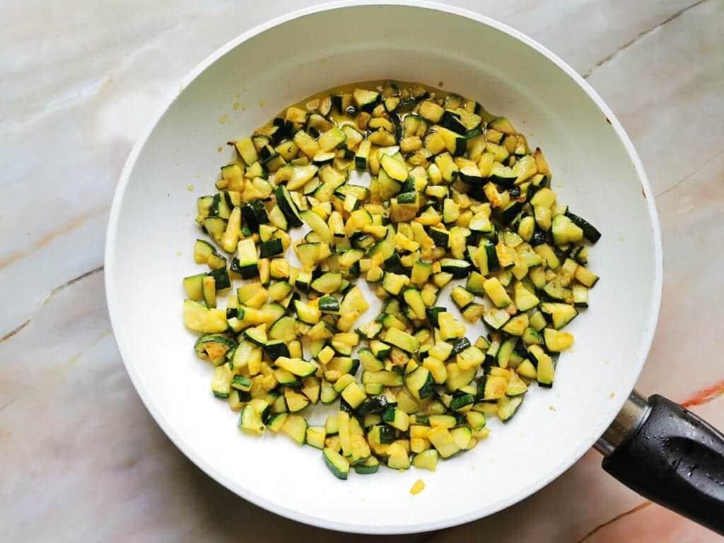 ready fried zucchini cubes in frying pan.