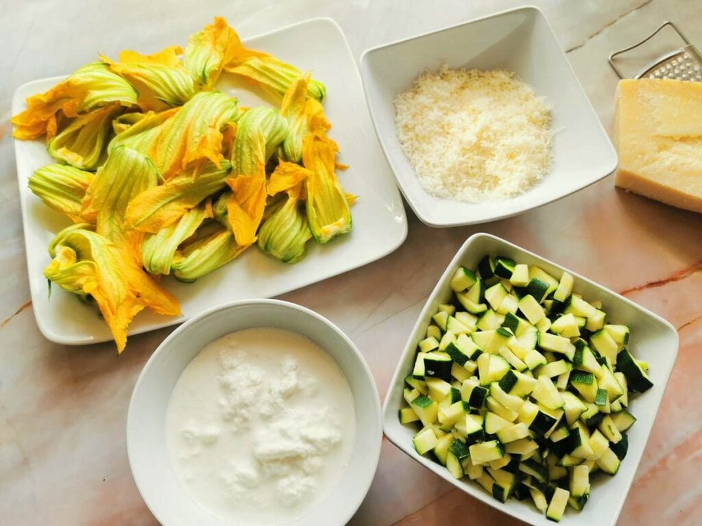 cut zucchini flowers, grated Parmigiano, stracciatella cheese and cubed zucchini in white bowls