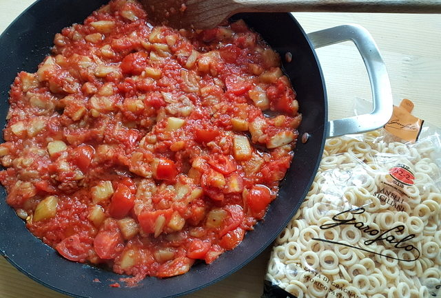tomato and eggplant sauce in frying pan with packet of pasta nearby
