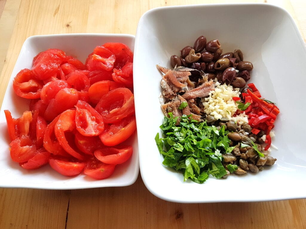 peeled and chopped tomatoes in white bowl and other prepared ingredients in white bowl