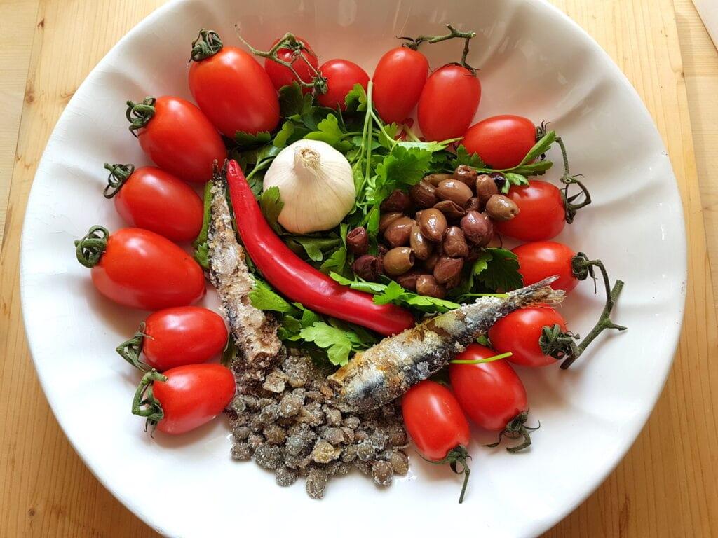 ingredients for spaghetti alla puttanesca in white bowl