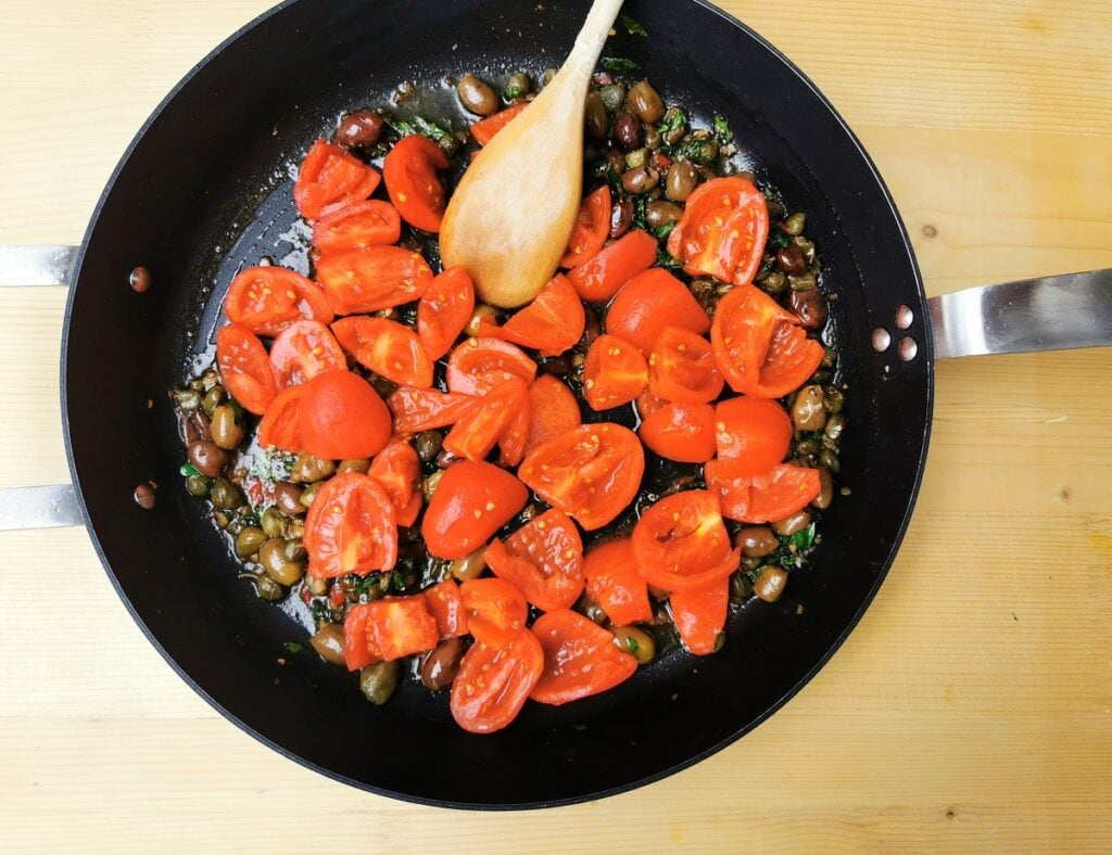 peeled and chopped tomatoes in frying pan with other puttanesca ingredients