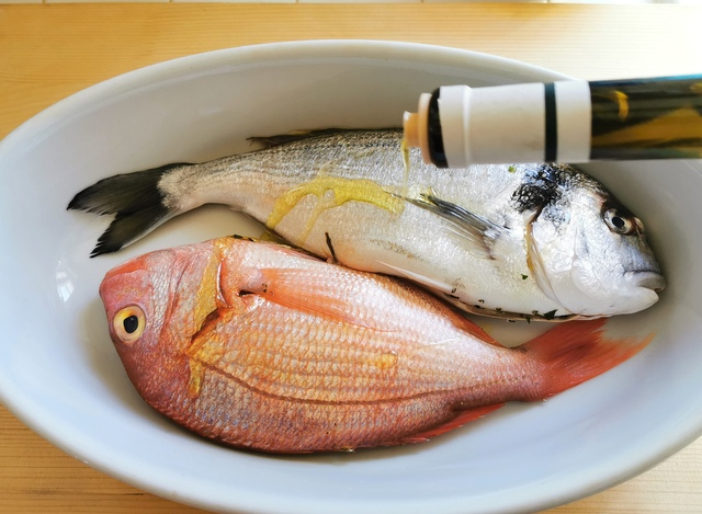 a small bream and a small snapper in white oven dish