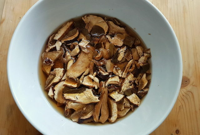 dried porcini soaking in white bowl in warm water
