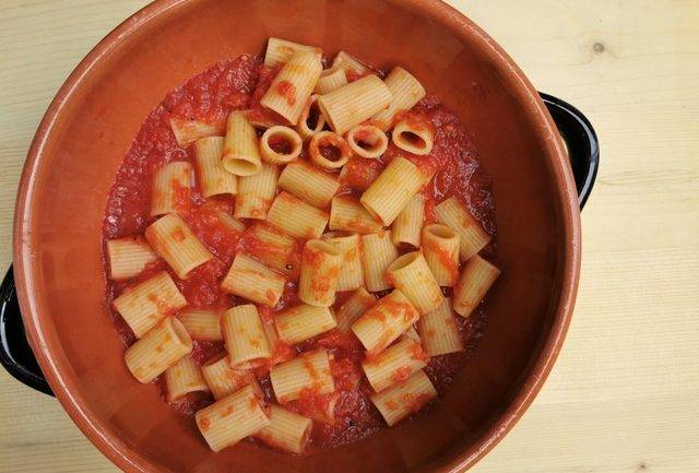 half cooked pasta with tomato sauce in terracotta oven dish