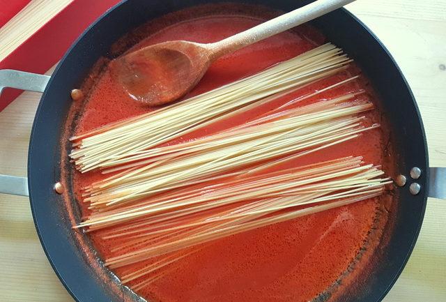 uncooked spaghetti in tomato sauce