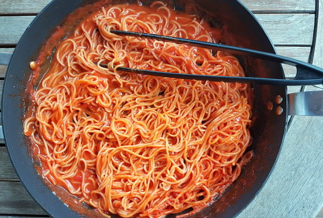 Spaghetti and tomato sauce cook together in the same pan