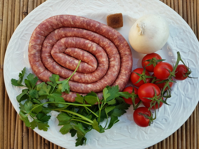 sausage and other ingredients on white plate