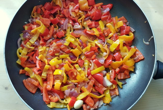 sweet peppers, garlic and onions cooking in frying pan