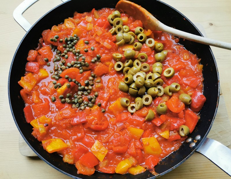 chopped green olives and small capers with caponata sauce in skillet