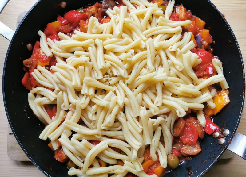 cooked casarecce pasta added to caponata in skillet