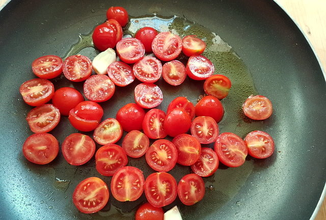 cherry tomatoes with olive oil and garlic in frying pan