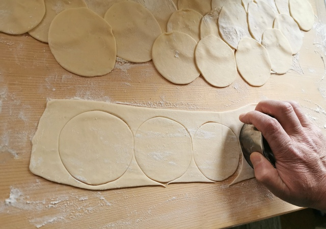 cutting pasta discs from rolled out pasta dough