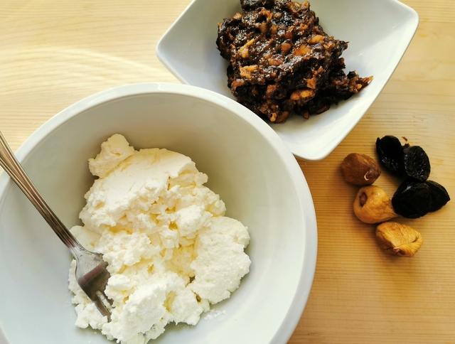 fresh ricotta in white bowl and chopped prunes and figs in white bowl