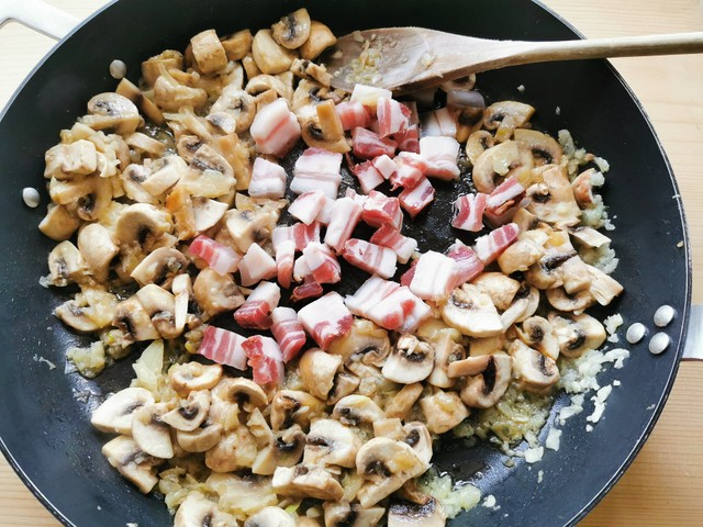 chopped pancetta in skillet with mushrooms and onions