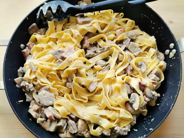 tagliatelle mixed with the pork fillet sauce in skillet before serving