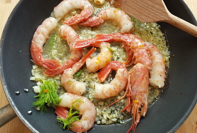 Prawns cooking in frying pan for farfalle pasta with prawns and orange recipe