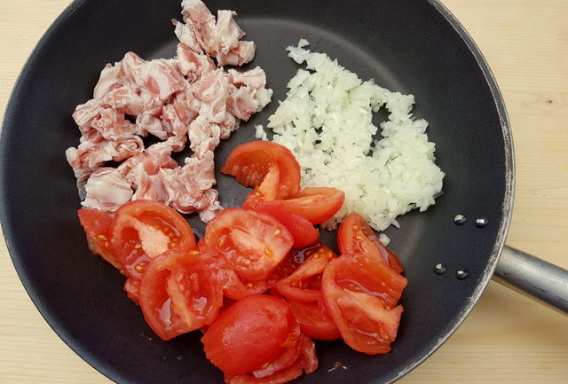 pancetta, onions and peeled and chopped tomatoes in frying pan