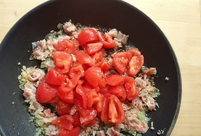 peeld tomatoes, pancetta and onions cooking in frying pan