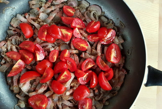 chopped tomatoes, sliced shallots and guanciale cooking in frying pan