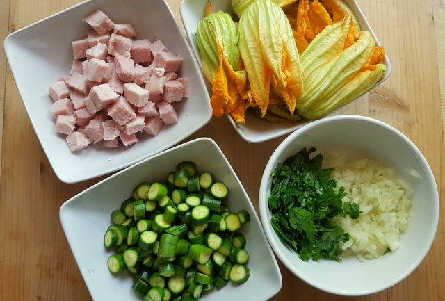 Ingredients for pasta with zucchini flowers, saffron and ham prepared in small white bowls