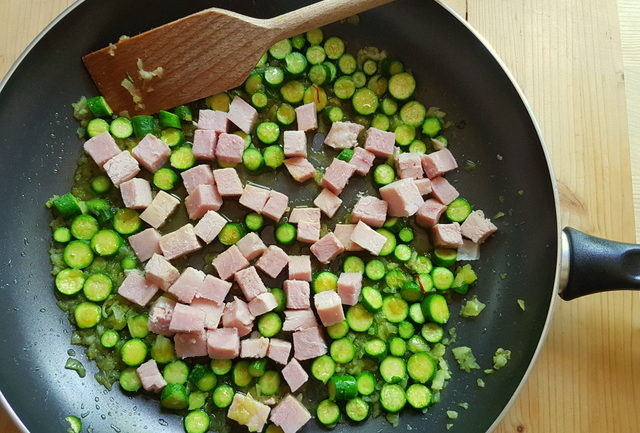 onions, zucchini and cooked ham cubes cooking in frying pan