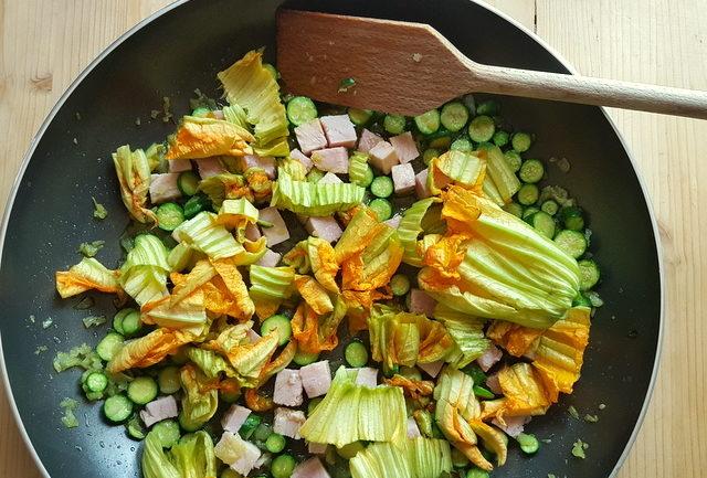 onion, zucchini, chopped ham and zucchini flowers in frying pan
